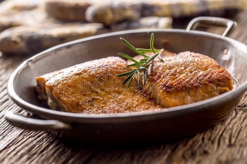Saumons Deux biftecks saumonés juteux dans la casserole de rôti avec le decoratio d'herbe images stock