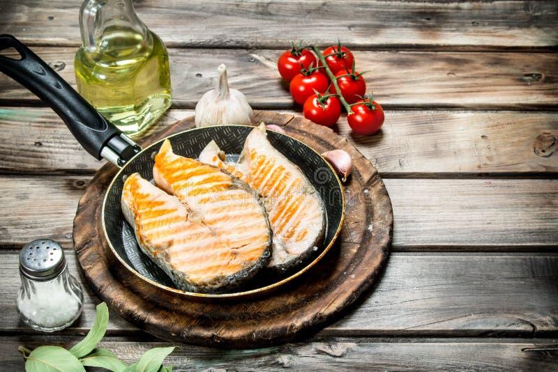 Saumons grillés dans une casserole avec des épices et des herbes photo stock