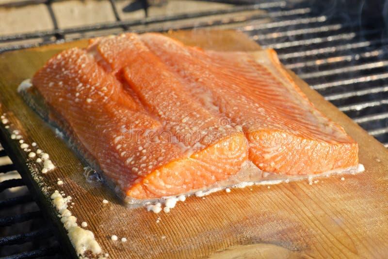Saumons sauvages sur la planche de cèdre au-dessus du barbecue images libres de droits