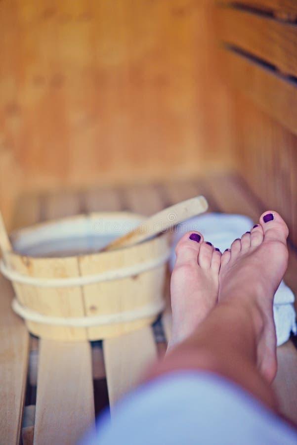 Sauna finlandesa com os pés de duas mulheres fotografia de stock