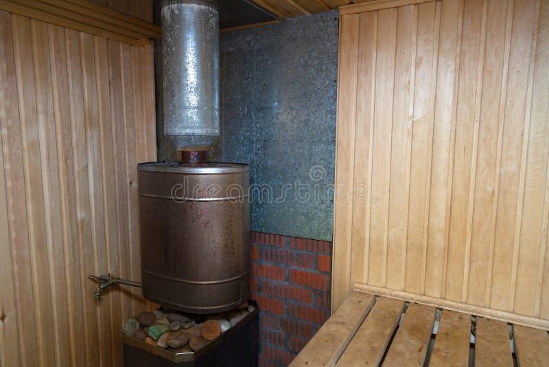 Sauna finlandesa con un cuarto de vapor adornado con madera con una estufa y piedras en ella para lavarse fotografía de archivo