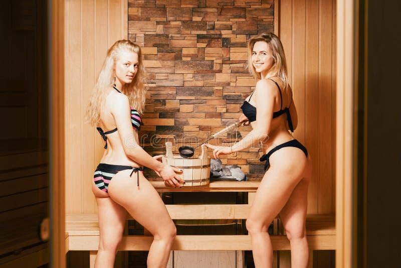 Sauna finlandese due bionde delle ragazze in costumi da bagno bagnano nel bagno una donna prende l'acqua in un mestolo Stile di v immagini stock