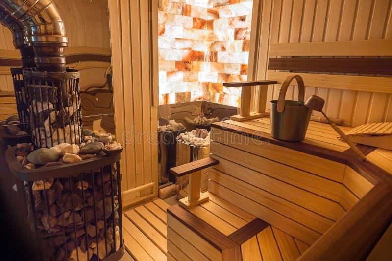 Sauna od drewna Kamienna ściana z oświetleniem od wśrodku Klasyczni akcesoria dla skąpania Kopyść i wiadro, kuchenka z gorącymi s zdjęcia royalty free