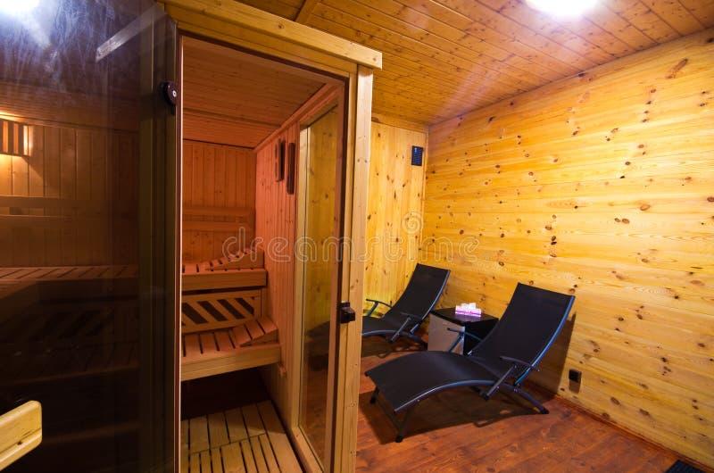 Saunabinnenland met twee sunbeds en kersen houten muren stock afbeeldingen
