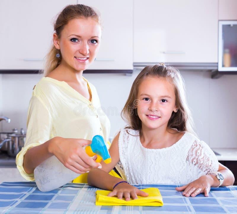 Saupoudrage de aide de maman de fille photo stock
