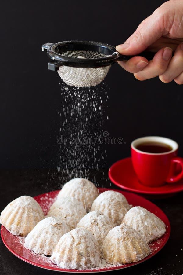Saupoudrage Eid Cookies avec du sucre glace photos libres de droits