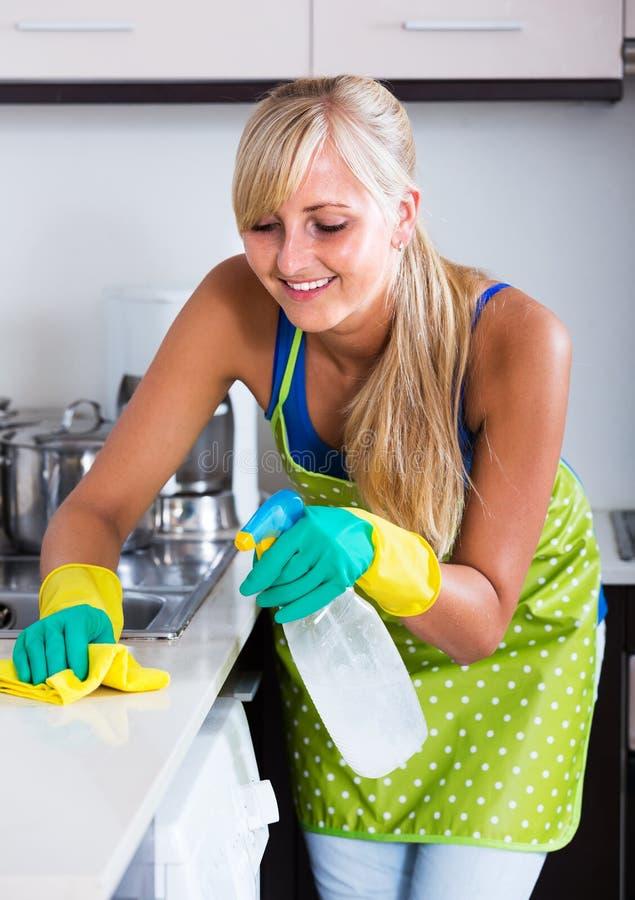 Saupoudrage gai de femme dans la cuisine images stock