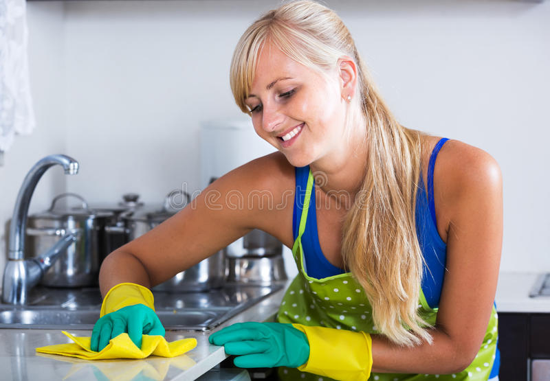 Saupoudrage gai de femme dans la cuisine photographie stock