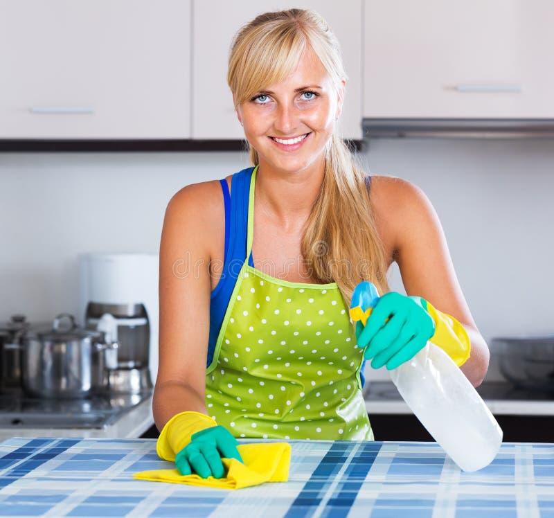 Saupoudrage gai de femme dans la cuisine photos stock