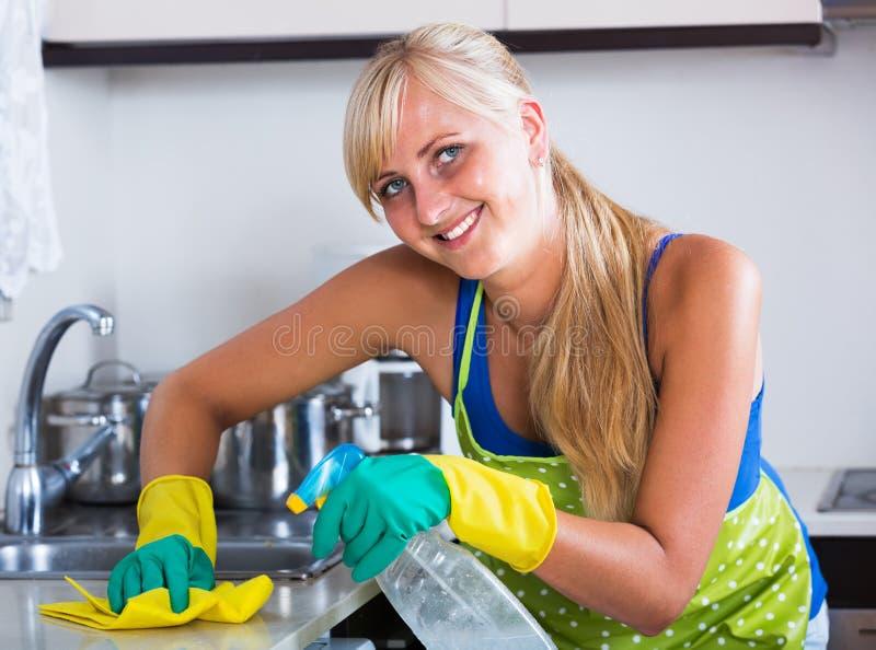 Saupoudrage gai de femme dans la cuisine photo libre de droits