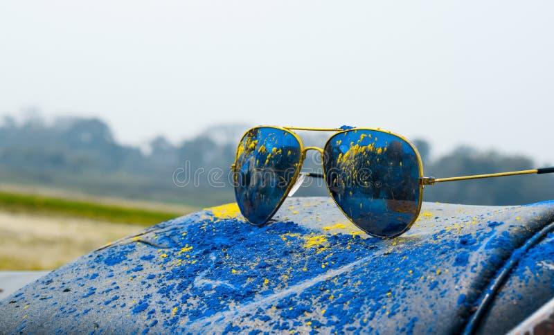 Saupoudrez la couleur bleue et jaune sur un verre de soleil pendant le festival de holi photographie stock libre de droits