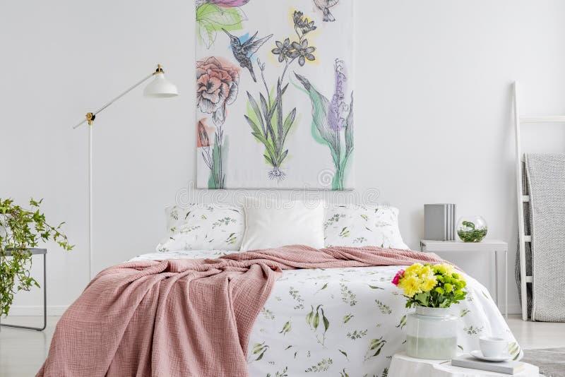 Saupoudrez la couverture rose jetée sur le lit grand avec la literie florale en vraie photo de l'intérieur blanc de chambre à cou photo libre de droits