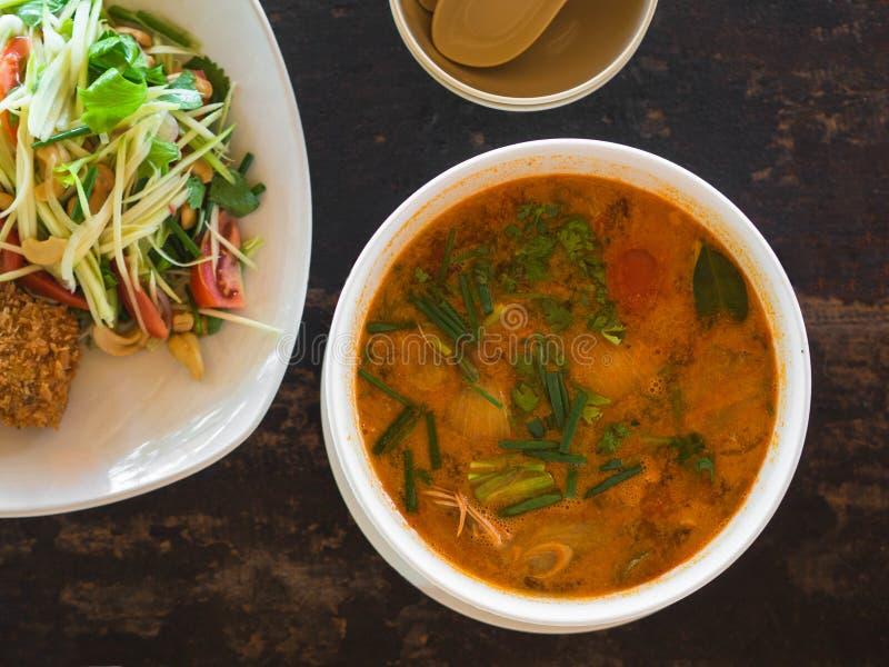 Saure und würzige Tom Yum Goong-Suppe und -salat mit grüner Mango und panierten Fischen auf Platte auf einer Tabelle in einem Res stockbild