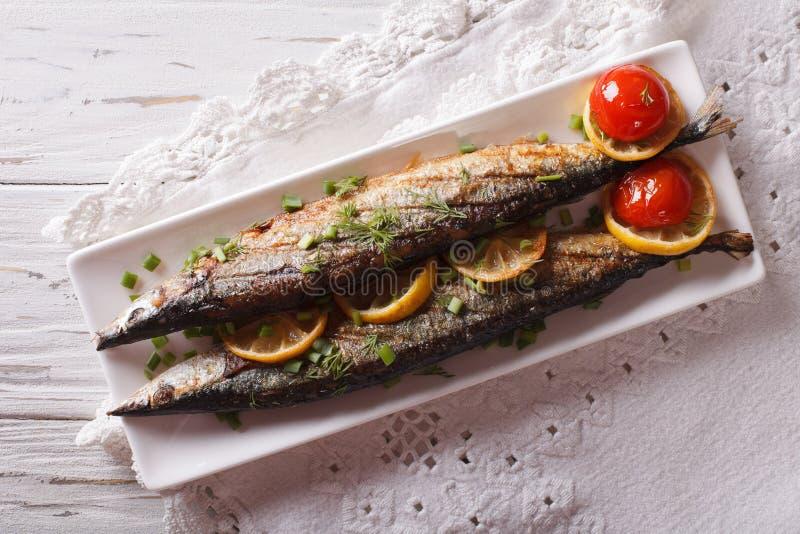 Saury grillade med grönsaker på en plattanärbild Horisontal till royaltyfria foton