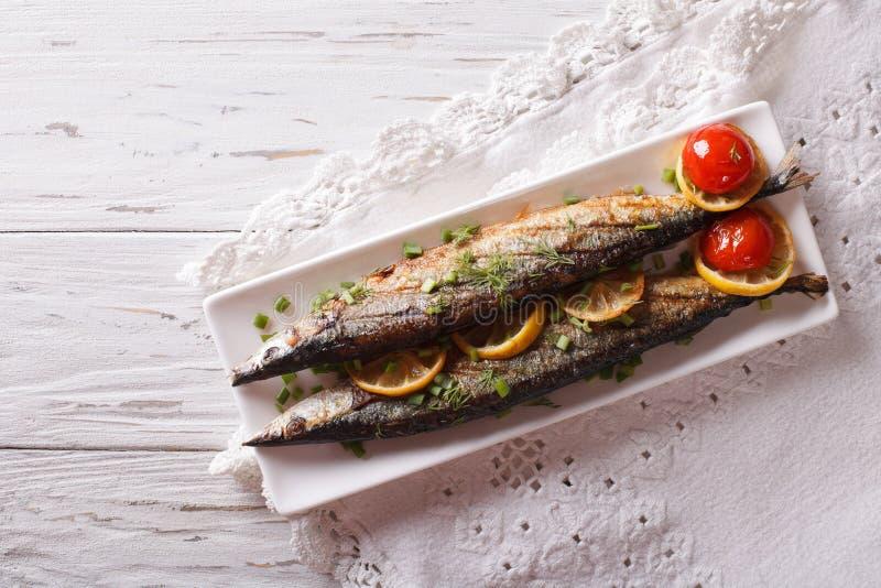 Saury som grillas med grönsaker på en platta horisontalbästa sikt arkivbilder