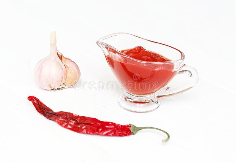 Saus, ketchup Ingrediënten voor het koken van ketchup op een witte houten achtergrond Tomaat, peper, knoflook royalty-vrije stock foto