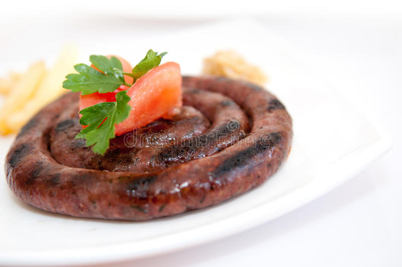 Sausage. Appetizing grilled sausage on white plate royalty free stock image