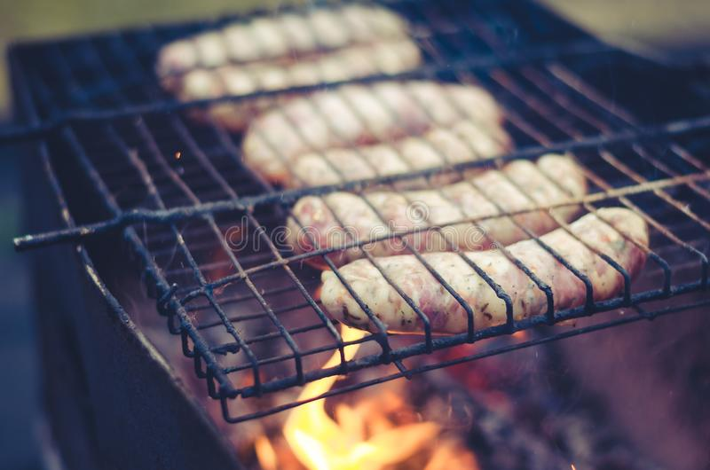 Sausage barbecue on a lattice a grill/sausages on a barbecue lattice on naked flame, selective focus. Sausage barbecue on a lattice a grill/ sausages on a royalty free stock photos