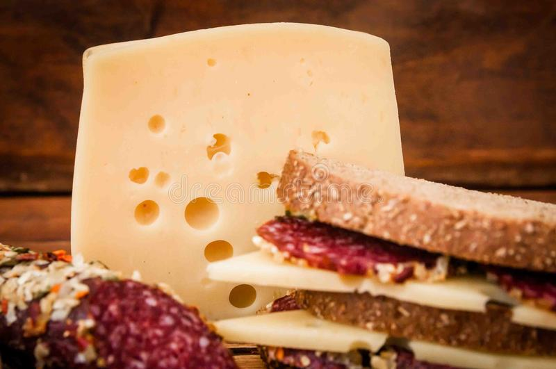 Dried sausage and cheese with holes for breakfast stock images