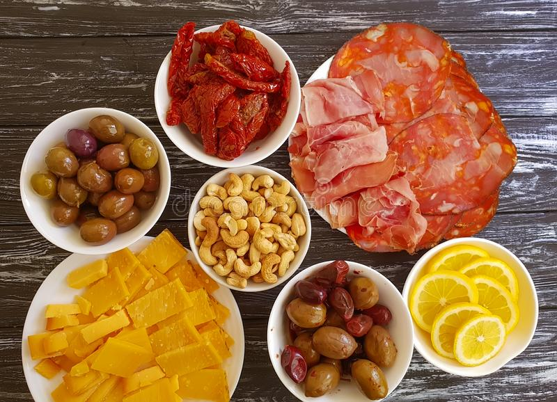 Sausage cheese jamon collection olives cashew nuts on wooden background stock image
