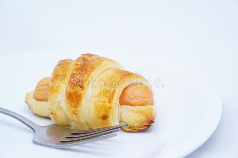 A sausage croissant with a fork royalty free stock images