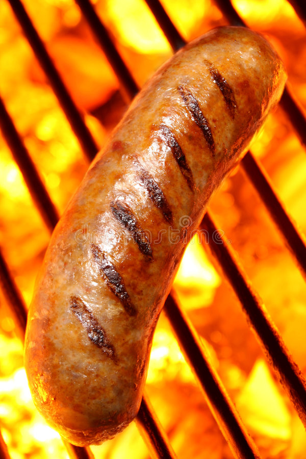 Sausage hot dog on a fire hot barbecue grill