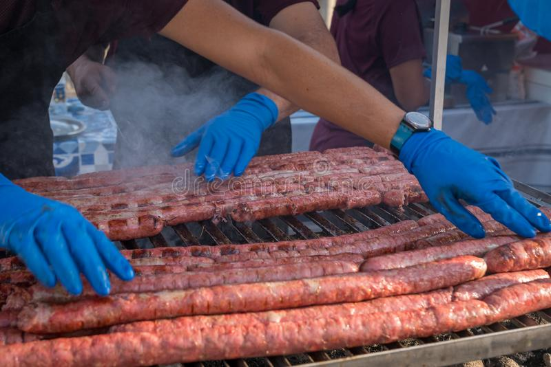 Sausage lined up on a outdoor grill. BBQ Sausage lined up on a large outdoor grill with smoke coming up from the fire below. person in black apron blue shirt stock photos