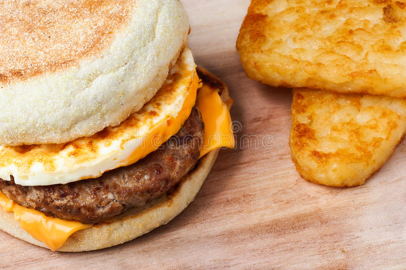 Sausage muffin with hash brown. English muffin with egg, sausage and cheese side with hash brown royalty free stock photo