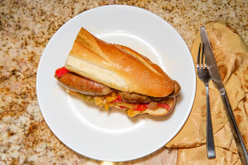 Sausage Onion Peppers Bun. Fried sausage onions and red green and yellow bell peppers on sandwich bun royalty free stock photos