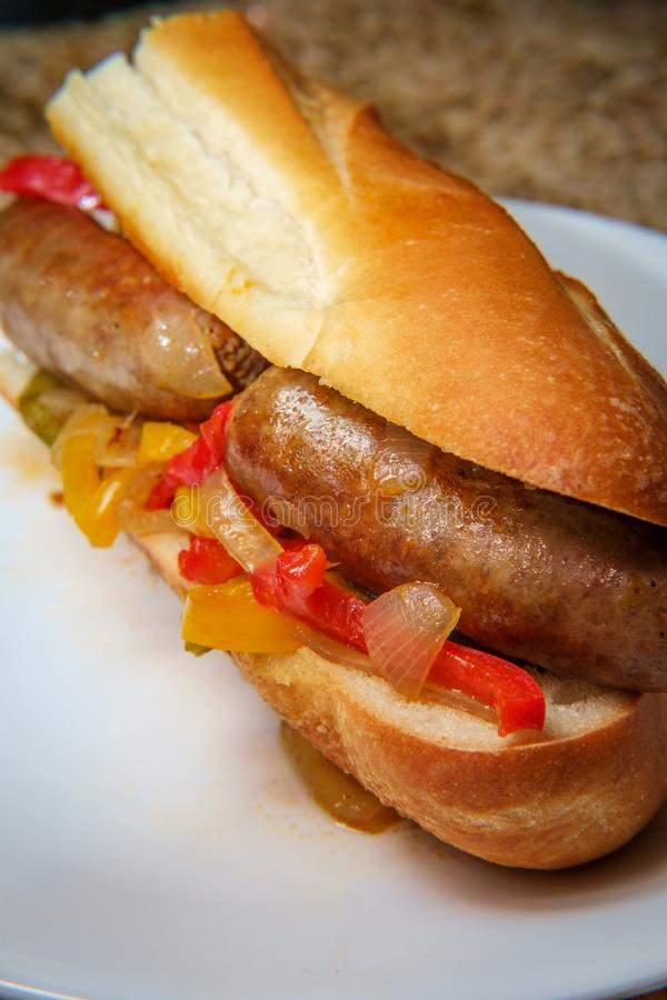 Sausage Onion Peppers Bun. Fried sausage onions and red green and yellow bell peppers on sandwich bun stock photos