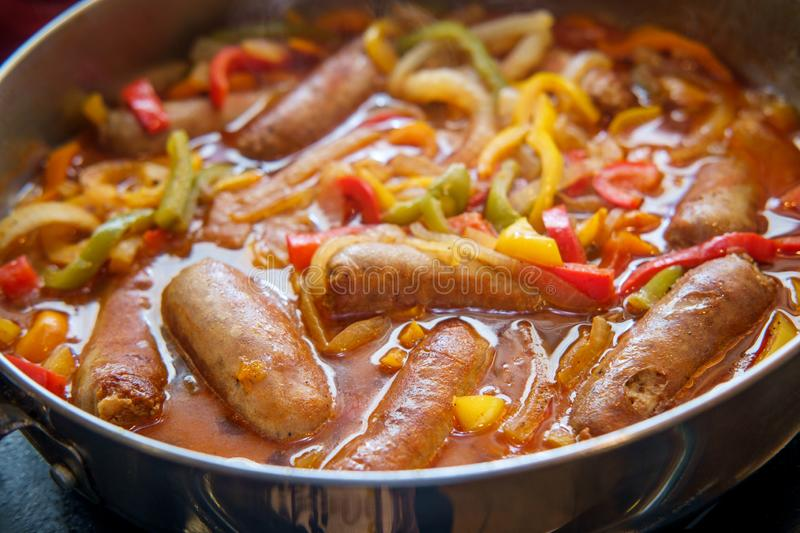 Sausage Onion Peppers Cooking. Cooking sausage onions and red yellow and green bell peppers in kitchen pan stock photos