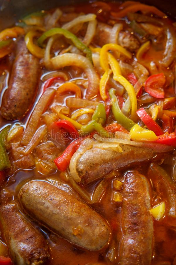 Sausage Onion Peppers Cooking. Cooking sausage onions and red yellow and green bell peppers in kitchen pan royalty free stock photos