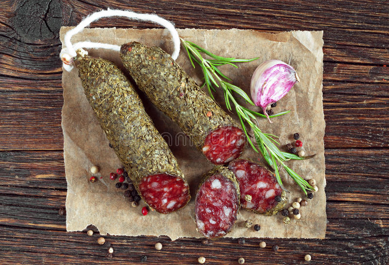 Sausage salami with spices. Sausage salami sliced with spices on old wooden table, top view royalty free stock photo