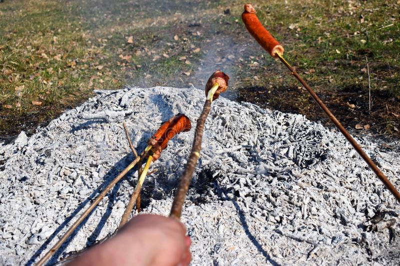 Sausage skewers are heated by grilling on a special slow fire for a long time to eat as a family breakfast on holiday and prepared royalty free stock images