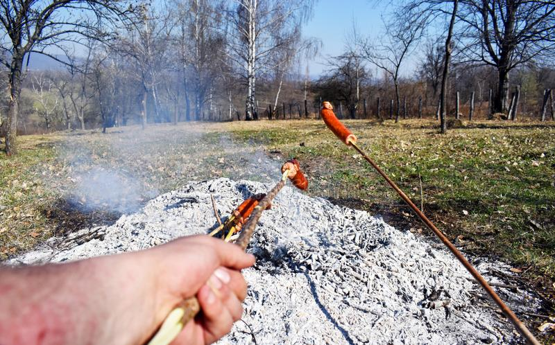 Sausage skewers are heated by grilling on a special slow fire for a long time to eat as a family breakfast on holiday and prepared stock photo
