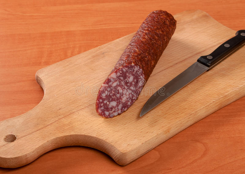 Sausage sliced with knife on a wooden table royalty free stock image