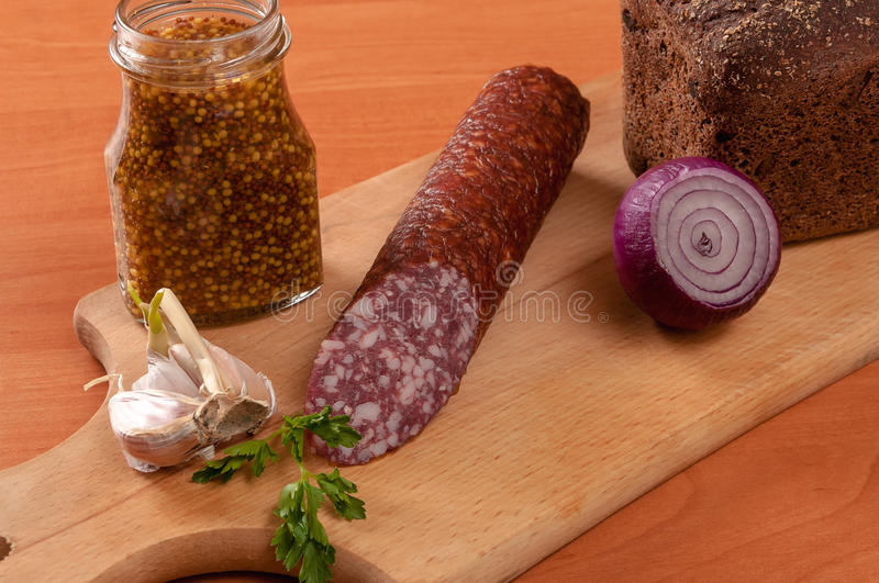 Sausage sliced with knife on a wooden table royalty free stock photo