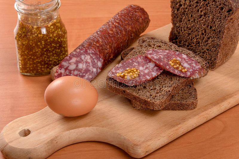 Sausage sliced with knife on a wooden table royalty free stock photography