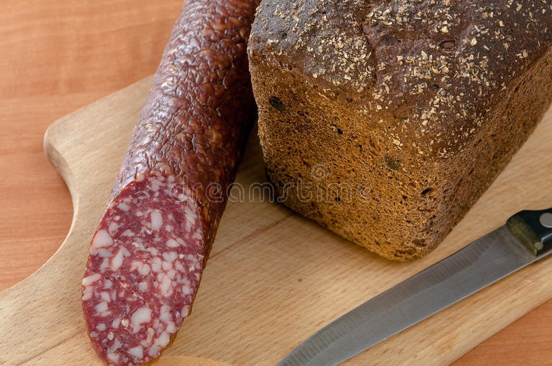 Sausage sliced with knife on a wooden table stock photography