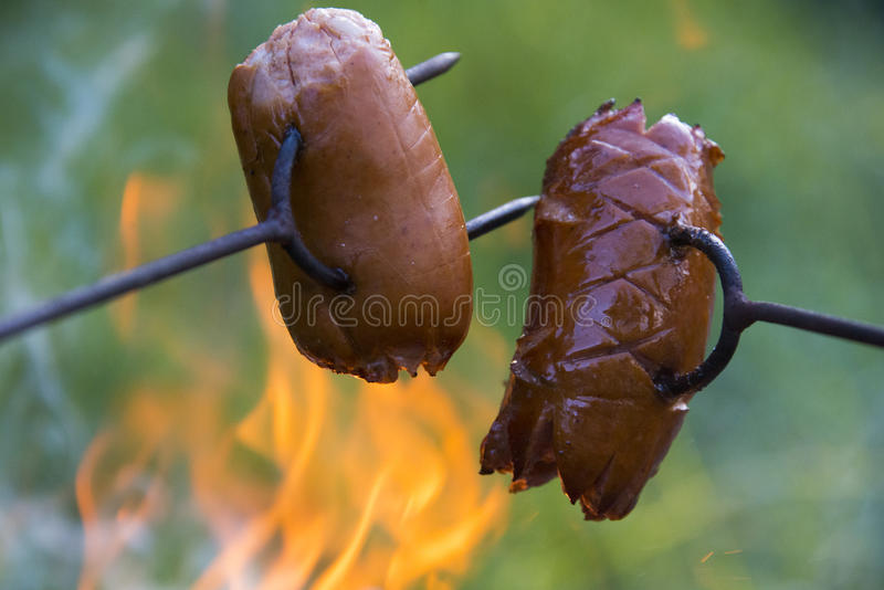 Sausage on a stick over the fire. Preparing sausages on camp fire stock images