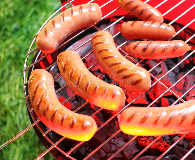 Sausages. On a grill on a background a grass royalty free stock images