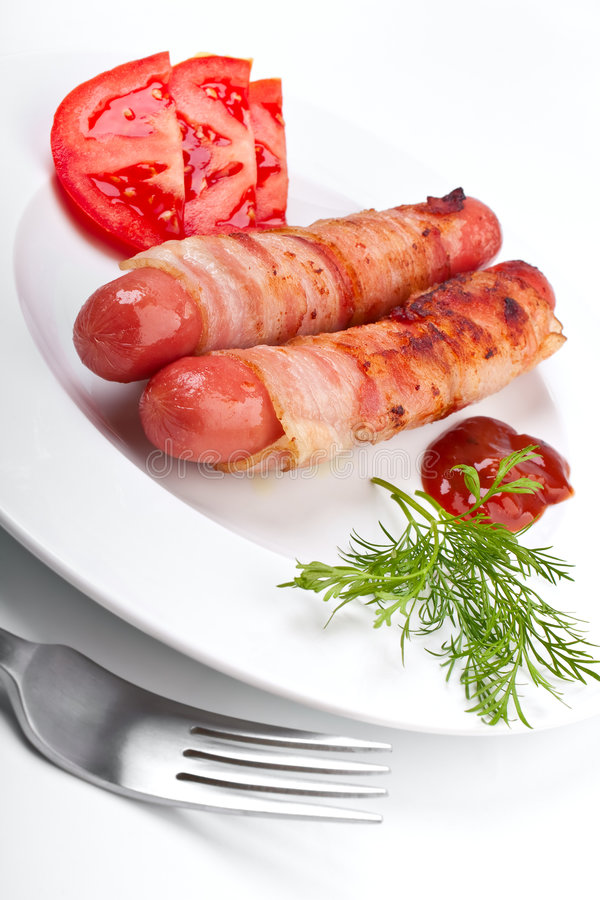 Sausages in bacon, coffee, tomatoes royalty free stock image