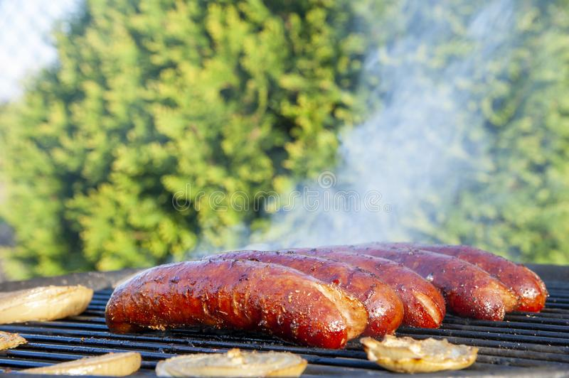 Sausages are baking on the grill on a sunny summer day.  stock photos