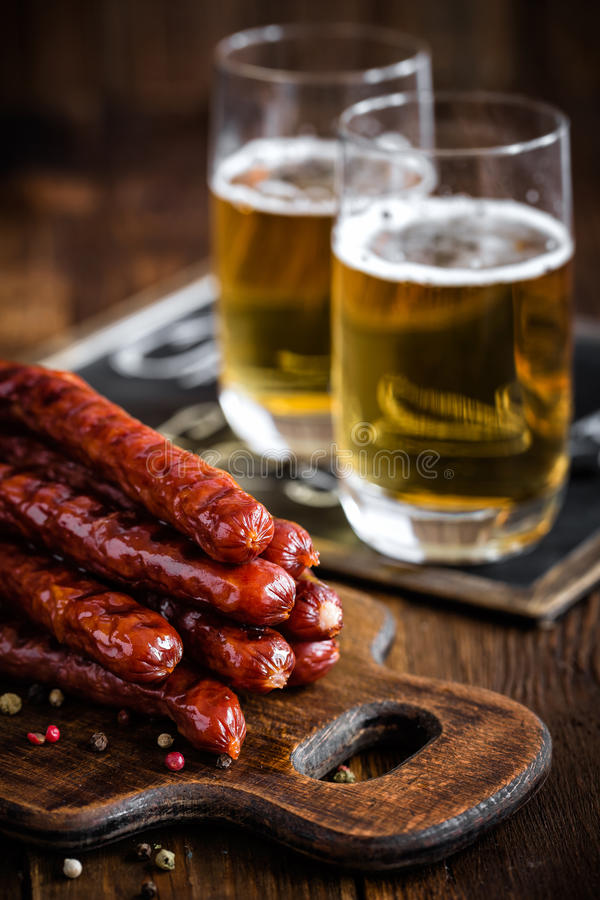 Sausages with beer. Roasted sausages with beer on wooden table stock photography