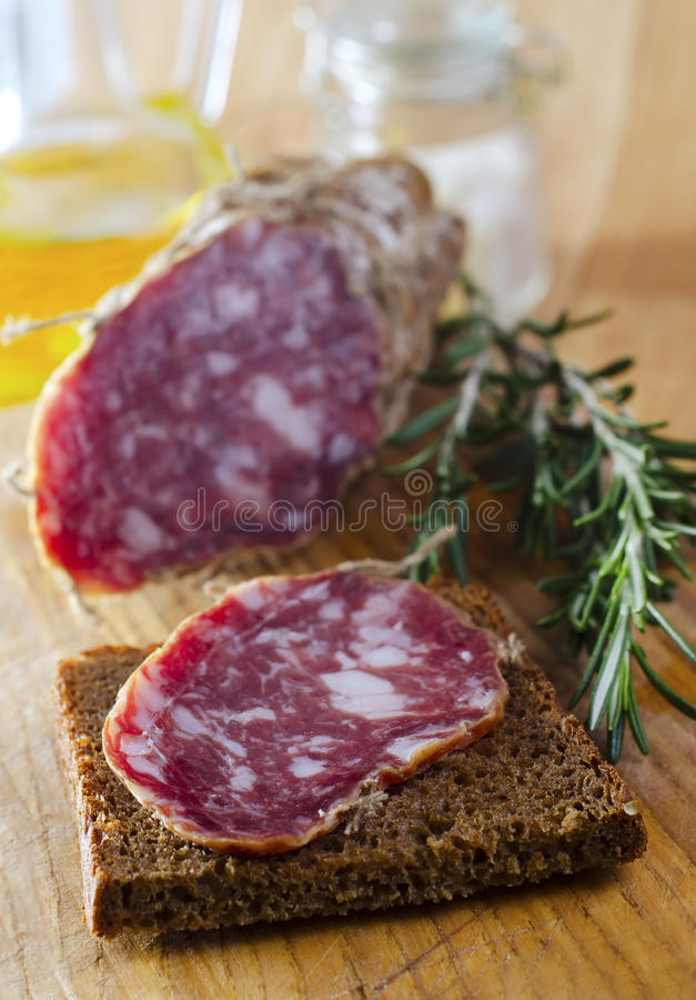 Sausages with bread. Bread with salami and rosemary royalty free stock image