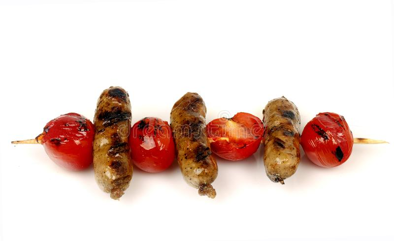 Sausages and cherry tomatoes grill on a spit. On a white background for isolation royalty free stock photos