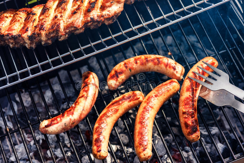 Sausages cooking on barbecue grill for summer outdoor party. Foo royalty free stock photos
