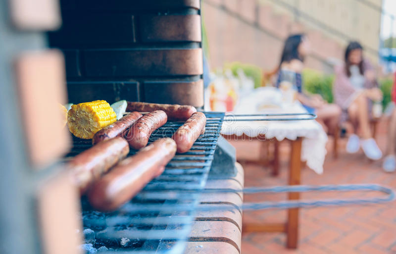 Sausages and corn cobs cooked in a barbecue stock image