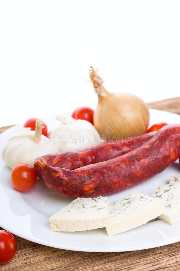 Sausages with Danish blue cheese and vegetable. Vertical photo of two sausages on white plate with danish blue cheese slices around plus various vegetable as stock images