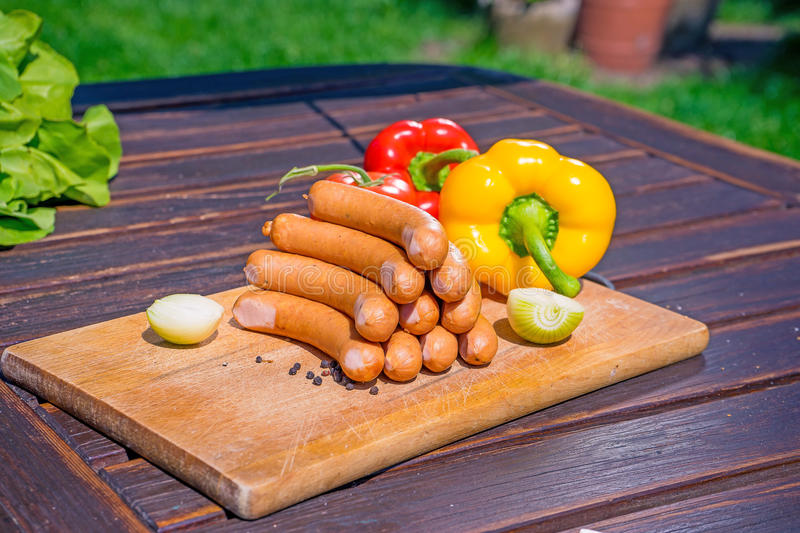 Sausages on the desk. Sausages with salad and pappers on the table in a sunny day royalty free stock photo